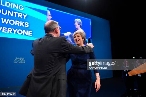 Britain's Prime Minister Theresa May is hugged by her husband Philip May on the stage at the end of her speech on the final day of the Conservative...