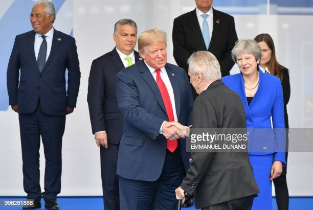 Britain's Prime Minister Theresa May looks on as US President Donald Trump shakes hands with Czech Republic President Milos Zeman as they join other...