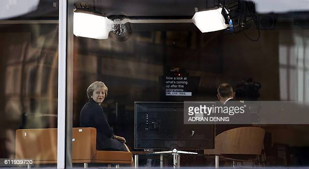 Britain's Prime Minister Theresa May looks out of the window alongside journalist Andrew Marr during a televsion interview at the BBC studio in...