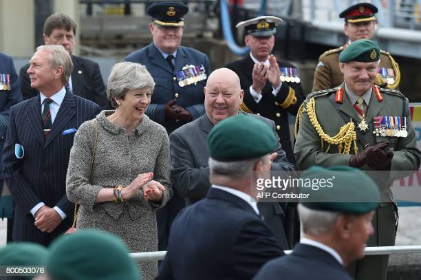 Britain's Prime Minister Theresa May Mayor of Liverpool Joe Anderson and Vice Chief of Defence Staff General Gordon Messenger watch a parade of...