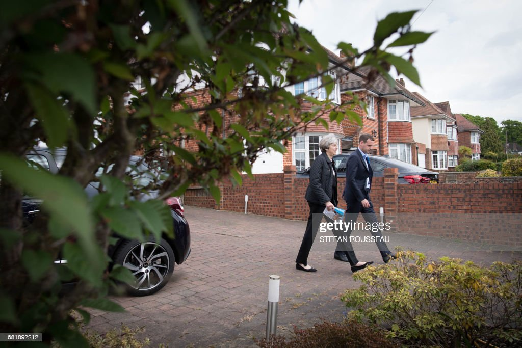 Britain's Prime Minister Theresa May meets local residents as she campaigns with Conservative candidate for the Southampton Test constituency, Paul Holmes (R), during a general election campaign visit in Southampton, souther England on May 11, 2017. Britain will vote in a general election on June 8. / AFP PHOTO / POOL / Stefan Rousseau