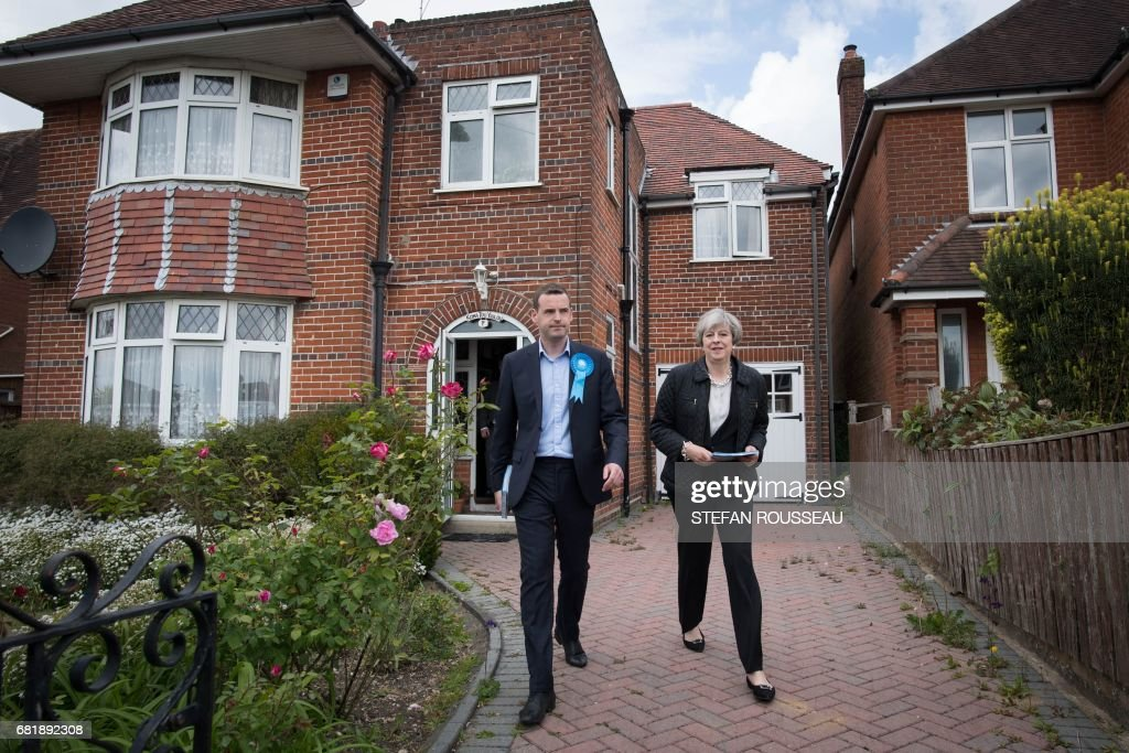 Britain's Prime Minister Theresa May meets local residents as she campaigns with Conservative candidate for the Southampton Test constituency, Paul Holmes (L), during a general election campaign visit in Southampton, souther England on May 11, 2017. Britain will vote in a general election on June 8. / AFP PHOTO / POOL / Stefan Rousseau