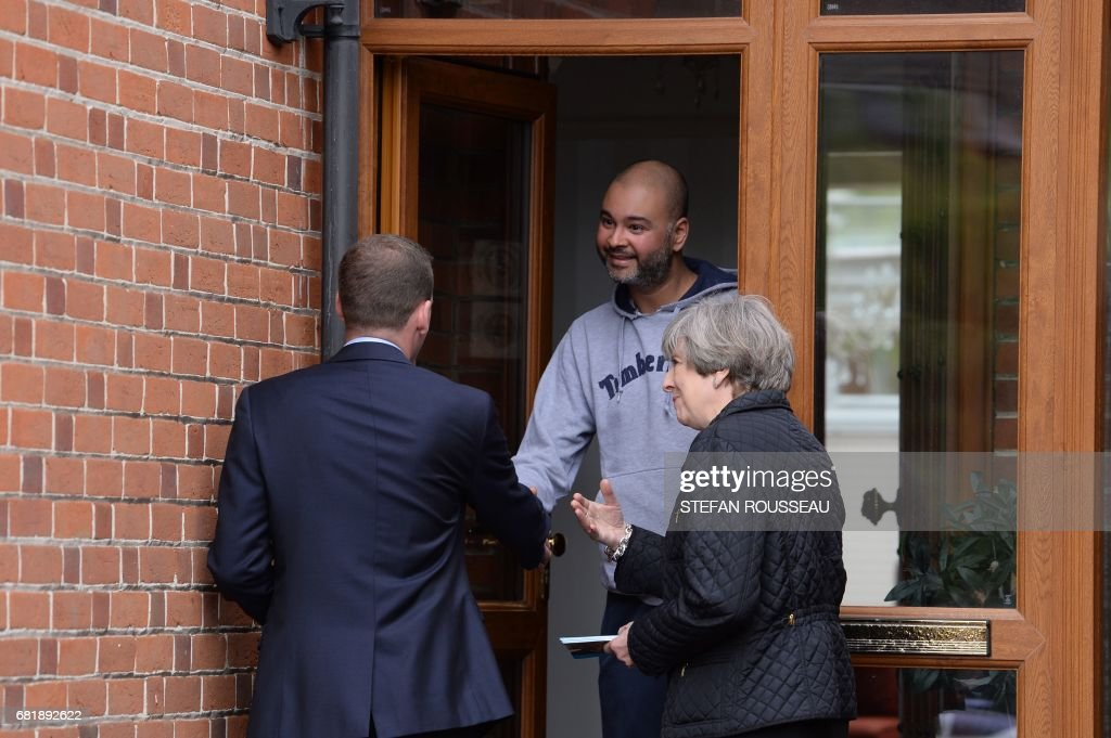 Britain's Prime Minister Theresa May meets local residents as she campaigns with Conservative candidate for the Southampton Test constituency, Paul Holmes (L), during a general election campaign visit in Southampton, southern England on May 11, 2017. Britain will vote in a general election on June 8. / AFP PHOTO / POOL / Stefan Rousseau