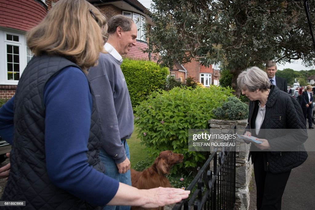Britain's Prime Minister Theresa May meets local residents as she campaigns with Conservative candidate for the Southampton Test constituency, Paul Holmes (unseen), during a general election campaign visit in Southampton, southern England on May 11, 2017. Britain will vote in a general election on June 8. / AFP PHOTO / POOL / Stefan Rousseau