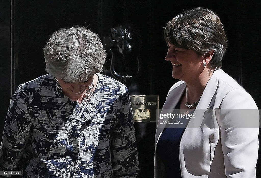 Britain's Prime Minister Theresa May (L) poses for a picture with Democratic Unionist Party (DUP) leader Arlene Foster at 10 Downing Street in central London on June 26, 2017. British Prime Minister Theresa May's Conservatives signed a deal Monday with Northern Ireland's Democratic Unionist Party that will allow them to govern after losing their majority in a general election this month. / AFP PHOTO / Daniel LEAL
