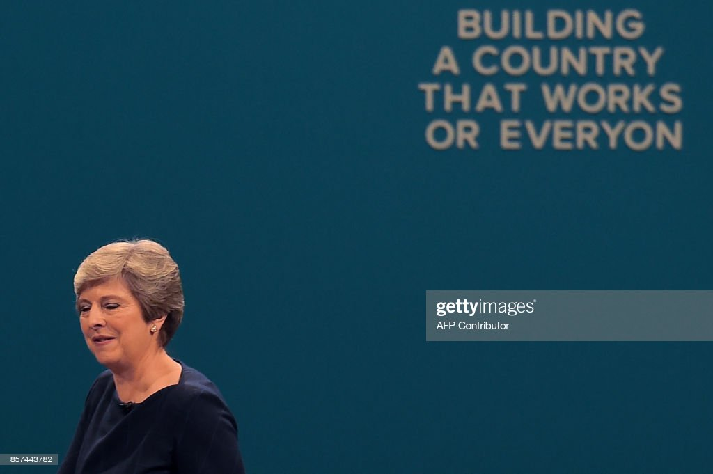 Britain's Prime Minister Theresa May reacts as she acknowledges applause from delegates, while passing a slogan whose letters have fallen off, after delivering her speech on the final day of the Conservative Party annual conference at the Manchester Central Convention Centre in Manchester, northwest England, on October 4, 2017. /