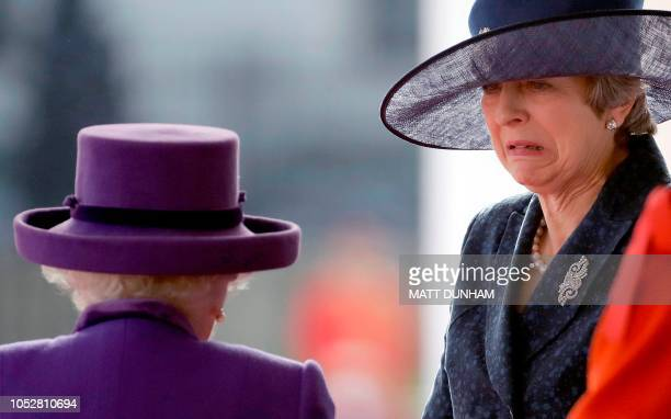 TOPSHOT Britain's Prime Minister Theresa May reacts as she is greeted by Britain's Queen Elizabeth II on the dias as they take their places for a...