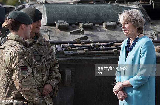 Britain's Prime Minister Theresa May reacts as she talks with soldiers during her visit to the 1st Battalion The Mercian Regiment at their barracks...