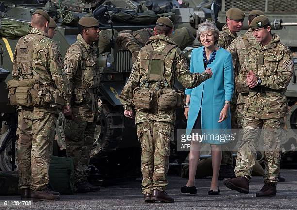 TOPSHOT Britain's Prime Minister Theresa May reacts as she talks with soldiers on her visit to the 1st Battalion The Mercian Regiment at their...