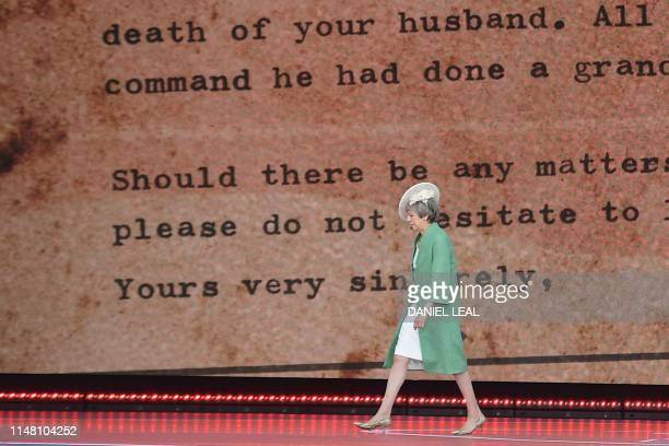 Britain's Prime Minister Theresa May returns to her seat after reading a letter written by Captain Skinner during an event to commemorate the 75th...