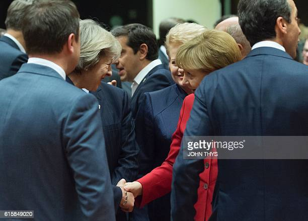 Britain's Prime minister Theresa May shakes hands with German Chancellor Angela Merkel during an European Union leaders summit on October 20 2016 at...