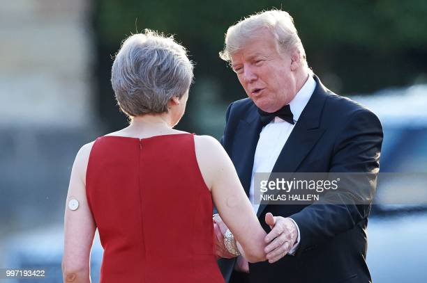 Britain's Prime Minister Theresa May shakes hands with US President Donald Trump as she welcomes Trump and his wife US First Lady Melania Trump for a...
