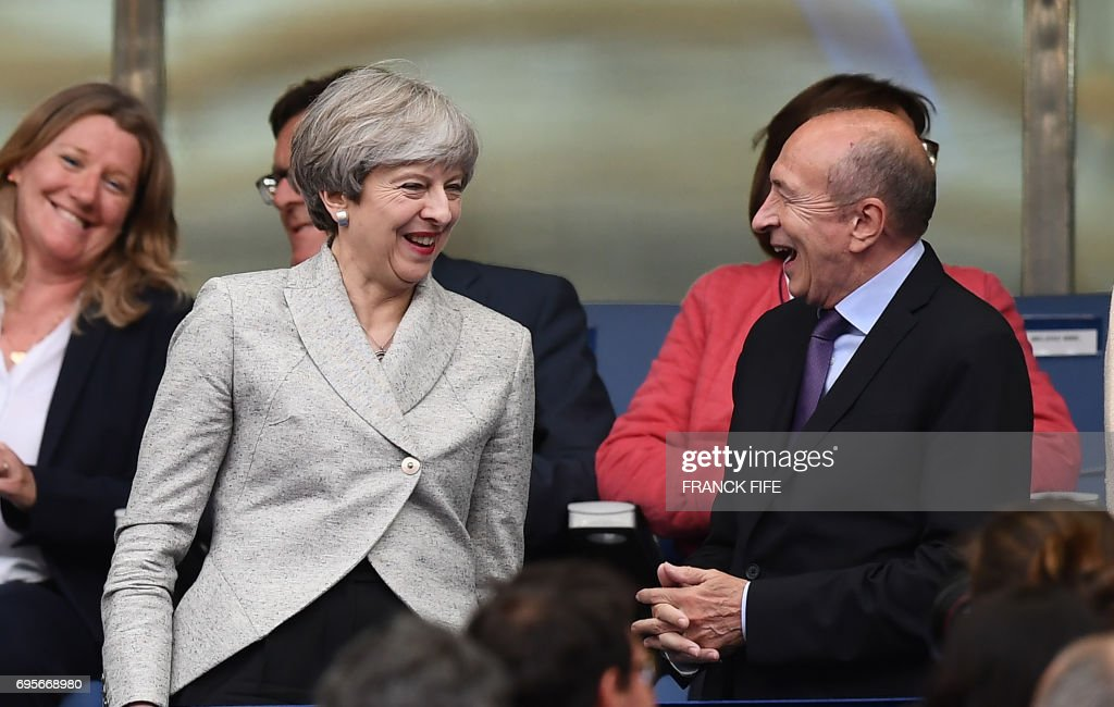 Britain's Prime Minister Theresa May (L) shares a light moment with French Interior Minister Gerard Collomb during the the international friendly football match between France and England at The Stade de France Stadium in Saint-Denis near Paris on June 13, 2017. /