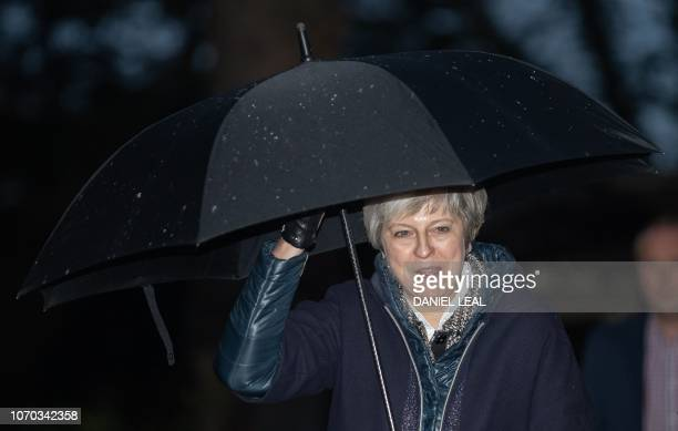 Britain's Prime Minister Theresa May shelters from the rain under an umbrella as she arrives for a church service near to her Maidenhead constituency...