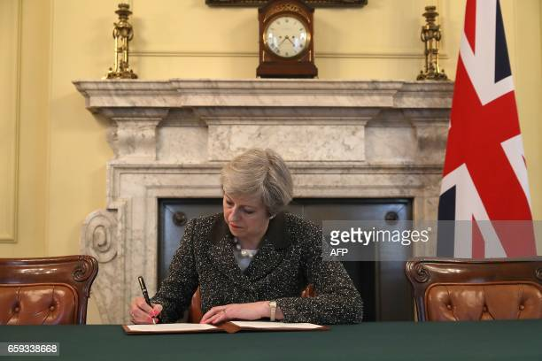 TOPSHOT Britain's Prime Minister Theresa May signs the official letter to European Council President Donald Tusk invoking Article 50 and signalling...