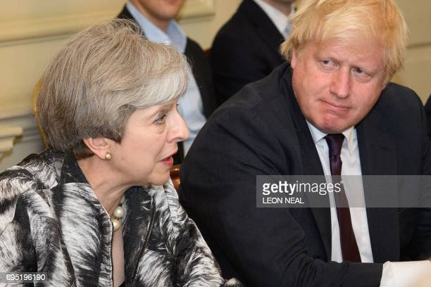 Britain's Prime Minister Theresa May sits with Britain's Foreign Secretary Boris Johnson as she holds the first Cabinet meeting of her new team at 10...