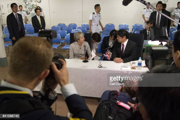 Britain's Prime Minister Theresa May sits with Japan's Defence Minister Itsunori Onodera ahead of a briefing on board the Japanese navy's helicopter...