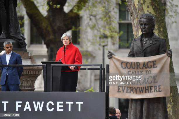 Britain's Prime Minister Theresa May speaks as London Mayor Sadiq Khan listens during the unveiling of a statue of suffragist and women's rights...