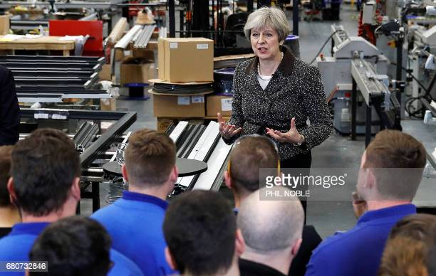 Britain's Prime Minister Theresa May speaks to workers and members of the media during a general election campaign meeting at a door manufacturer's...