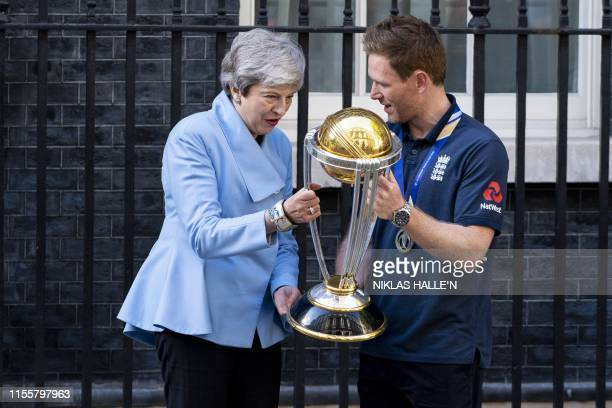 Britain's Prime Minister Theresa May speaks with England's captain Eoin Morgan as they hold the World Cup trophy outside 10 Downing Street as England...