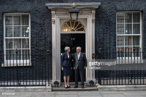 Britain's Prime Minister Theresa May stands with European Commission president JeanClaude Juncker at the front door of 10 Downing Street on April 26...