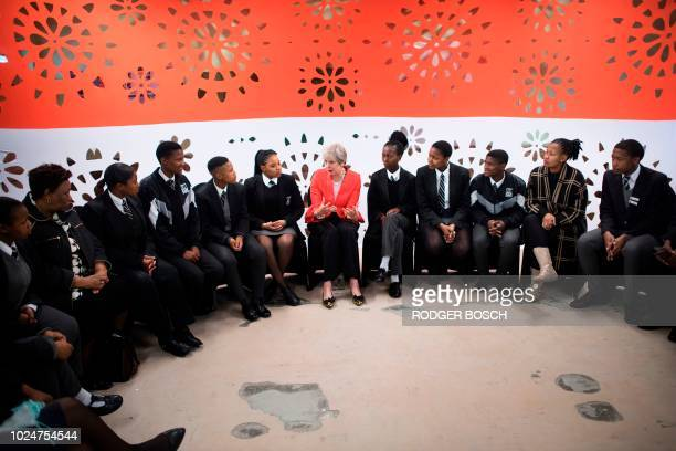 TOPSHOT Britain's Prime Minister Theresa May talks to a group of school children during a visit to the ID Mkhize Secondary School in Gugulethu about...