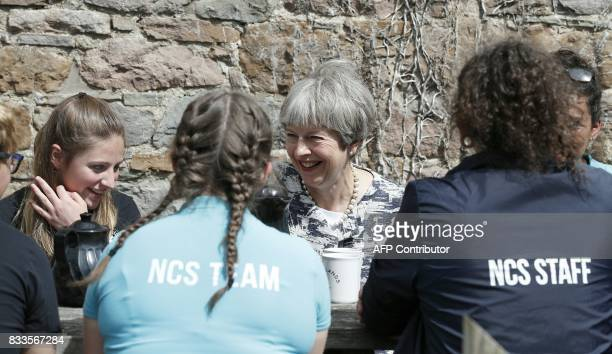 Britain's Prime Minister Theresa May talks with ALevel students at the Woodlands Outdoor Education Centre in Glasbury eastern Wales on August 17 2017...