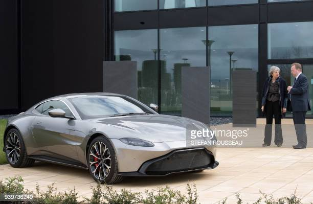 Britain's Prime Minister Theresa May talks with Andy Palmer CEO of Aston Martin as they look at the company's new Vantage sports car in Barry south...