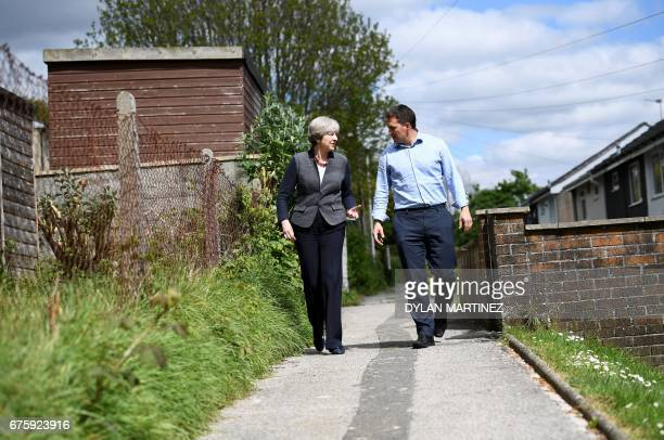 Britain's Prime Minister Theresa May talks with Conservative MP for Plymouth Johnny Mercer as they walk in Plymouth southwest England on May 2 during...