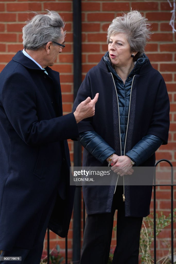 Britain's Prime Minister Theresa May (R) talks with Conservative MP for Wokingham, John Redwood during a visit to the new housing development, Montague Park in Wokingham on January 3, 2018 / AFP PHOTO / POOL / Leon Neal
