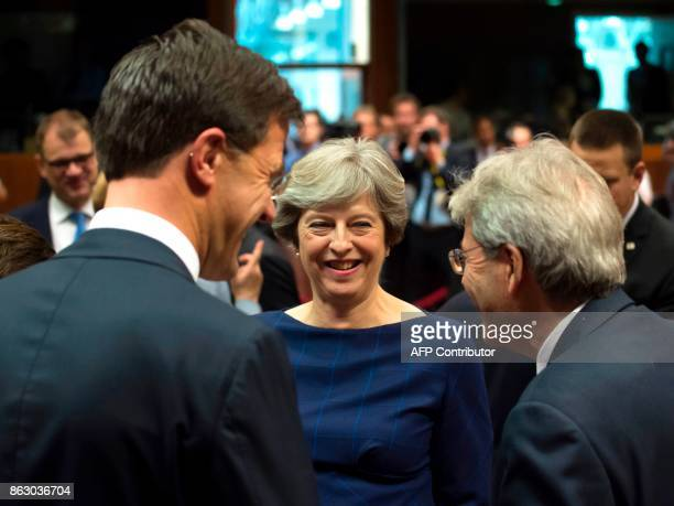 Britain's Prime minister Theresa May talks with Dutch Prime minister Mark Rutte and Italian Prime Minister Paolo Gentiloni in Brussels on October 19...