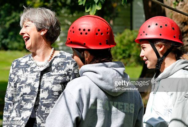 Britain's Prime Minister Theresa May talks with participants as they prepare to take part in an activity at the Woodlands Outdoor Education Centre in...