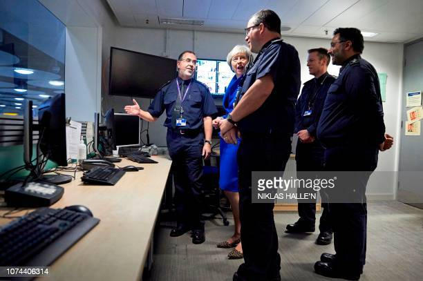 Britain's Prime Minister Theresa May talks with UK Border Force officers as she visits their Command Centre during her visit to Terminal 5 at London...
