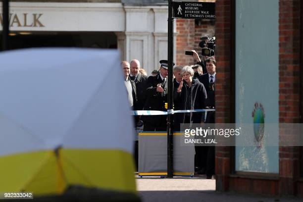 TOPSHOT Britain's Prime Minister Theresa May talks with Wiltshire Police's Chief Constable Kier Pritchard as she is shown the police tent covering...