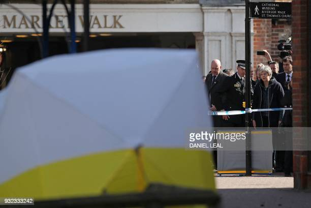 Britain's Prime Minister Theresa May talks with Wiltshire Police's Chief Constable Kier Pritchard as she is shown the police tent covering the bench...
