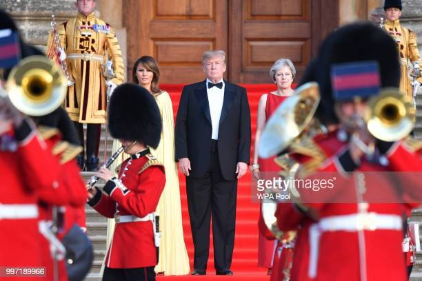 Britain's Prime Minister Theresa May US President Donald Trump and First Lady Melania Trump look on as a military band plays at Blenheim Palace on...