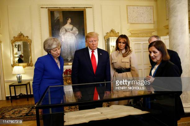 Britain's Prime Minister Theresa May US President Donald Trump US First Lady Melania Trump and Philip May are shown a copy of the American...