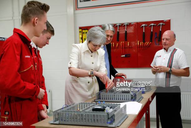 Britain's Prime Minister Theresa May uses a screw driver as she and Britain's Chancellor of the Exchequer Philip Hammond are shown products by...