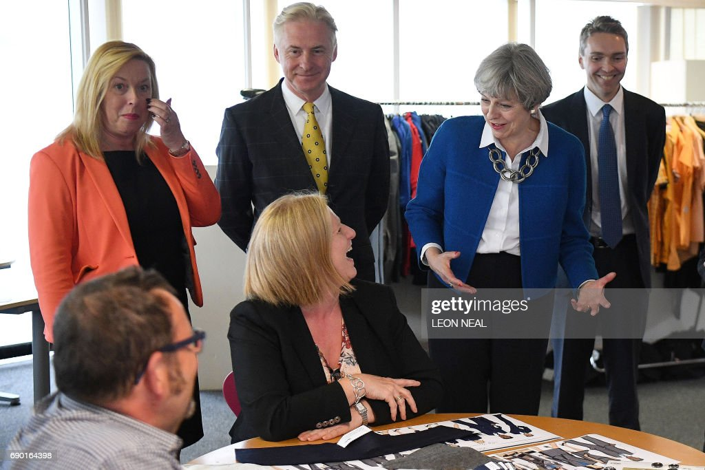 Britain's Prime Minister Theresa May (2R) visits Simon Jersey, a business uniform supplier in the constituency of Hyndburn in Accrington, Lancashire county on May 30, 2017. / AFP PHOTO / POOL / Leon Neal