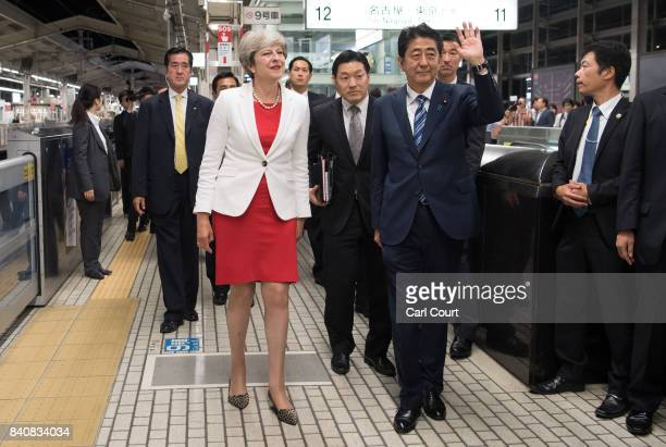Britain's Prime Minister Theresa May waits with Japan's Prime Minister Shinzo Abe as they arrive at Kyoto Train Station to board a bullet train to...