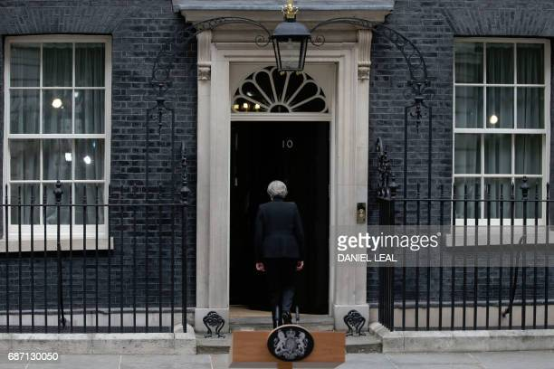 TOPSHOT Britain's Prime Minister Theresa May walks back after delivering a statement outside 10 Downing Street in central London on May 23 2017 after...