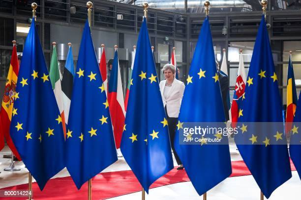 Britain's Prime Minister Theresa May walks behind flags of Europe as she arrives on the second day of a summit of European Union leaders and focusing...
