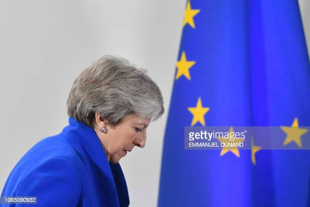 Britain's Prime Minister Theresa May walks past a European Union flag as she arrives to give a press conference following a special meeting of the...