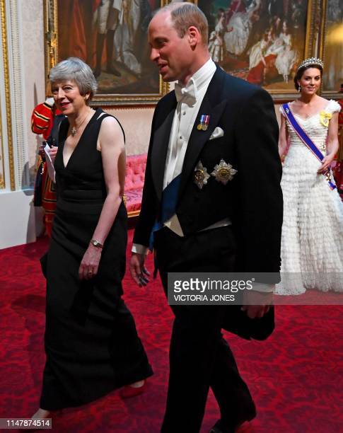 Britain's Prime Minister Theresa May walks with Britain's Prince William, Duke of Cambridge followed by Britain's Catherine, Duchess of Cambridge as...