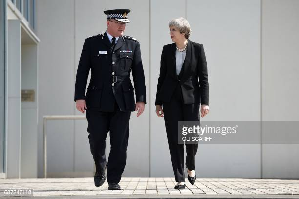 TOPSHOT Britain's Prime Minister Theresa May walks with Chief Constable of Greater Manchester Police Ian Hopkins as she leaves following their...