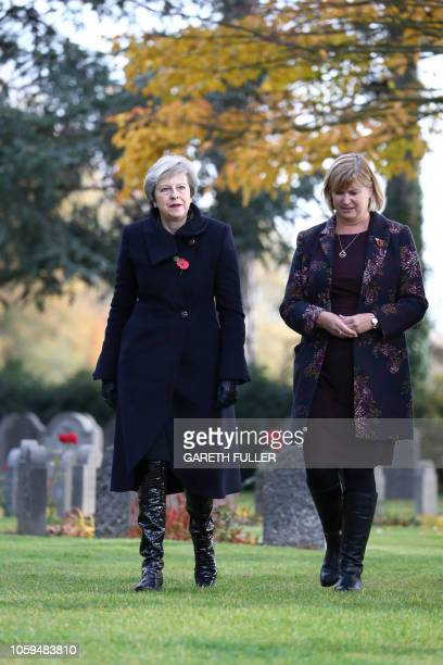 Britain's Prime Minister Theresa May walks with Liz Sweet of the Commonwealth War Graves Commission at the St Symphorien Military Cemetery in Mons...