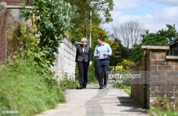 Britain's Prime Minister Theresa May walks with local Conservative Party candidate Johnny Mercer during a campaign visit on May 2 2017 in Plymouth...