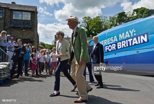 Britain's Prime Minister Theresa May walks with nursery owner Tom Horsfield as she arrives for election campaign visit to Horsfields Nursery on June...