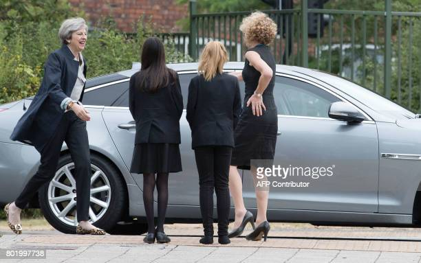 Britain's Prime Minister Theresa May walks with pupils Miya Herbert Katie Davies and head teacher Dr Helen Holman on her arrival to attend a teacher...