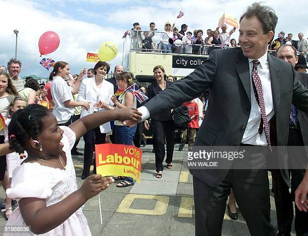 Britain's Prime Minister Tony Blair greets a young wellwisher as he visits Saltdean Community Club Brighton East Sussex 31 May 2001 Mr Blair used a...